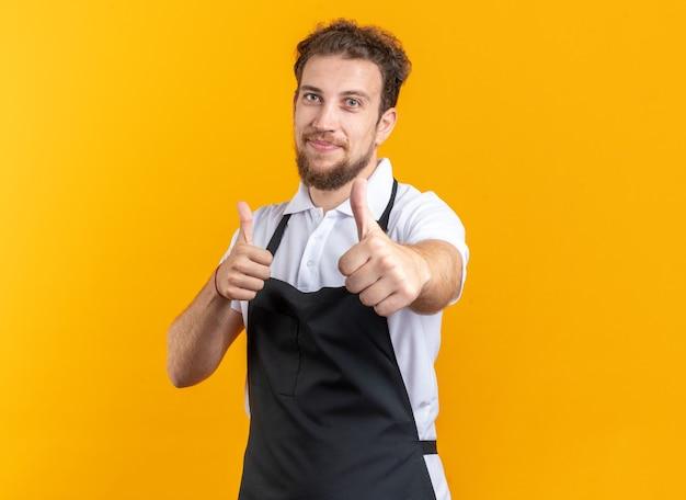 Zufriedener junger männlicher friseur in uniform, der daumen nach oben auf gelbem hintergrund zeigt