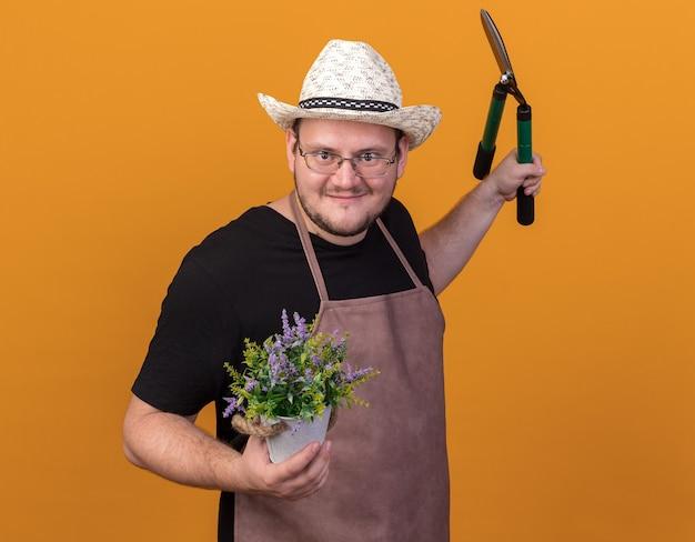 Zufriedener junger männlicher gärtner mit gartenhut und handschuhen, der klipper mit blume im blumentopf hält, der die hand isoliert auf oranger wand ausbreitet
