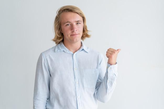 Zufriedener junger mann, der beiseite zeigt