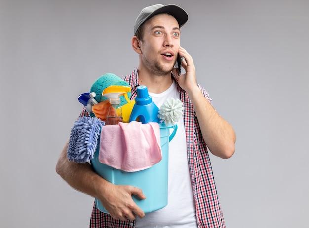 Zufriedener junger mann, der eine kappe trägt, die einen eimer mit reinigungswerkzeugen hält, spricht am telefon isoliert auf weißer wand