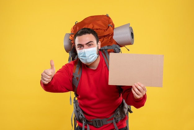 Zufriedener junger mann, der eine medizinische maske mit rucksack trägt und ein blatt hält, ohne eine ok geste auf isoliertem gelbem hintergrund zu schreiben