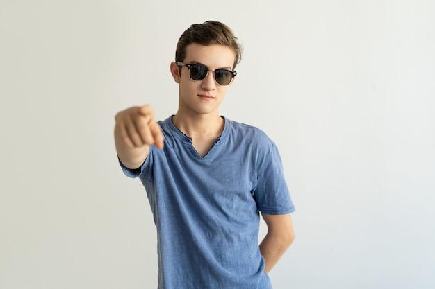 Zufriedener junger mann in den gläsern zeigend auf kamera