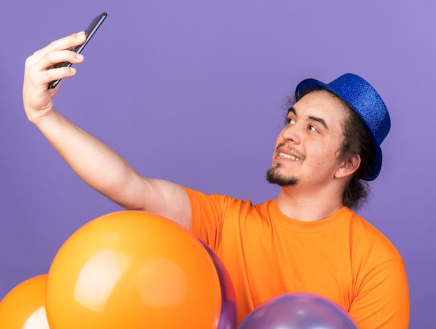 Zufriedener junger mann mit partyhut, der hinter luftballons steht, macht ein selfie isoliert auf lila wand