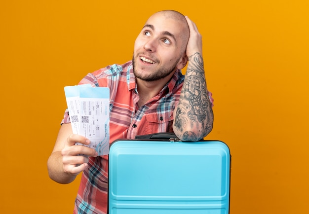 Zufriedener junger reisender, der flugtickets hält und seinen arm auf den koffer legt, der auf die seite isoliert auf der orangefarbenen wand mit kopierraum schaut