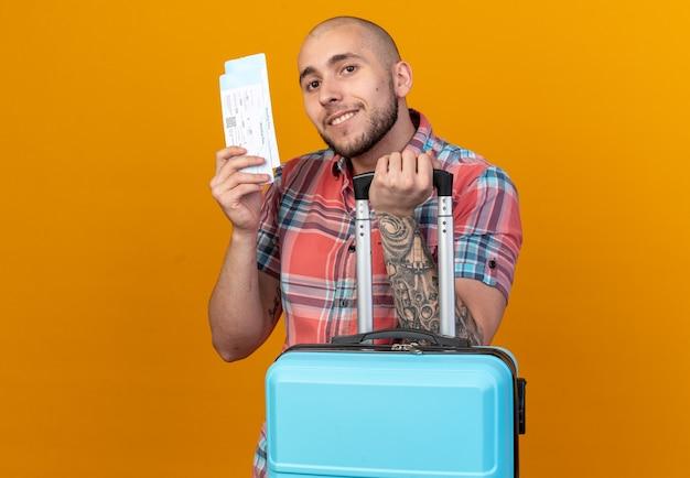 Zufriedener junger reisender, der koffer und flugtickets isoliert auf oranger wand mit kopienraum hält