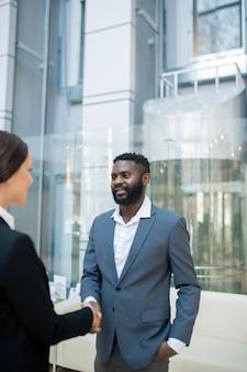 Zufriedener junger schwarzer geschäftsmann im anzug, der gegen aufzug steht und händedruck mit geschäftspartner macht