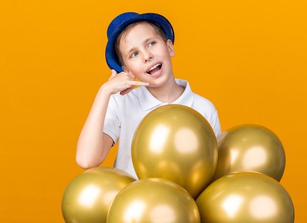 Zufriedener junger slawischer junge mit blauem partyhut, der gestikuliert, rufen sie mich an, indem sie auf die seite schauen, die mit heliumballons isoliert auf oranger wand mit kopierraum steht