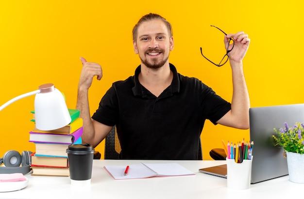 Zufriedener junger student, der am tisch mit schulwerkzeugen sitzt und eine brille hält, die den daumen isoliert auf der orangefarbenen wand zeigt