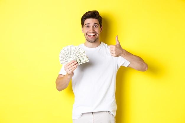 Zufriedener käufermann, der daumen nach oben zeigt und geld hält, mit bargeld einkauft, auf gelbem hintergrund steht.