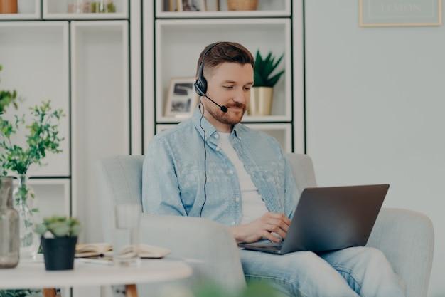 Zufriedener kerl in bequemer kleidung, der ein headset für die videokommunikation verwendet und den laptop auf seinem schoß hält, während er zu hause bleibt. männlicher freiberufler, der online arbeitet. fernarbeit und freiberufliches konzept