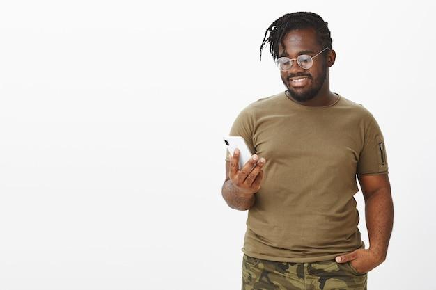 Zufriedener kerl mit brille, die mit seinem telefon gegen die weiße wand posiert