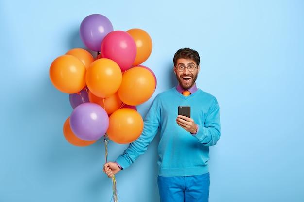 Zufriedener kerl mit luftballons, die im blauen pullover aufwerfen