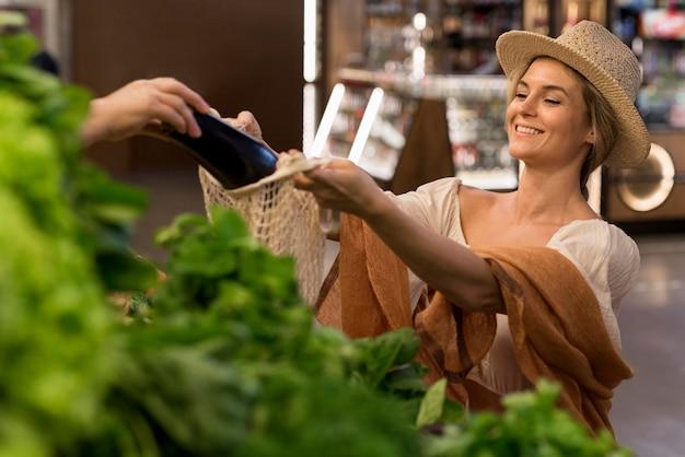 Zufriedener kunde, der auberginen kauft