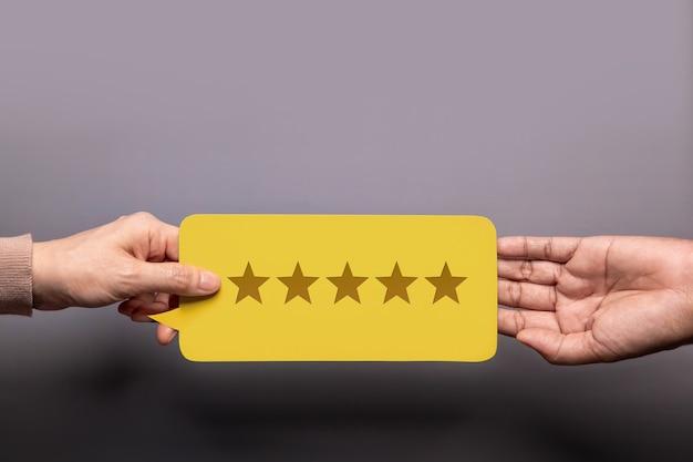 Zufriedener kunde, der einem geschäftsmann eine feedback-karte mit fünf-sterne-bewertung gibt