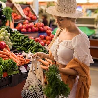 Zufriedener kunde, der gemüse kauft