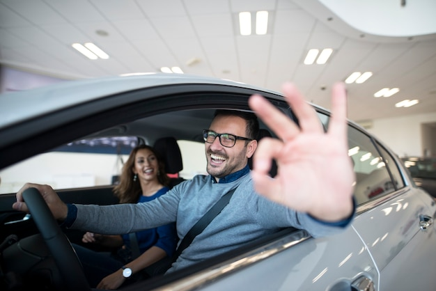 Zufriedener kunde, der neues auto im autohaus kauft