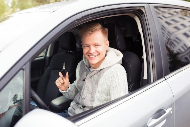 Zufriedener kunde hat gerade ein auto im autohaus gekauft. er sitzt in einem neuen auto und zeigt einen schlüssel