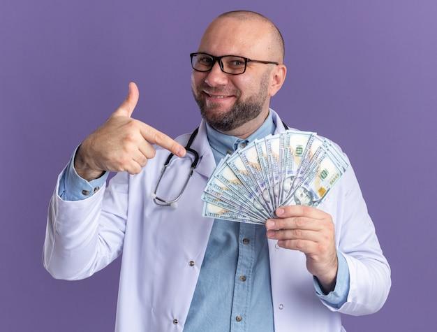 Zufriedener männlicher arzt mittleren alters, der ein medizinisches gewand und ein stethoskop mit einer brille trägt und auf geld zeigt