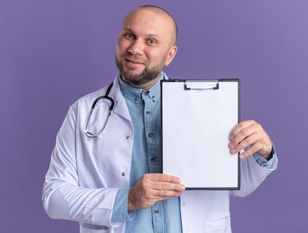 Zufriedener männlicher arzt mittleren alters, der ein medizinisches gewand und ein stethoskop trägt, das die zwischenablage nach vorne zeigt, die auf der violetten wand isoliert ist?
