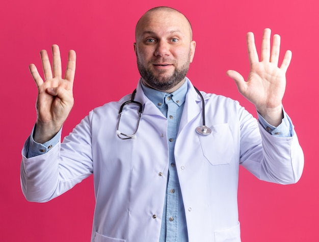 Zufriedener männlicher arzt mittleren alters, der ein medizinisches gewand und ein stethoskop trägt, der nach vorne schaut und neun mit den händen isoliert auf der rosa wand zeigt