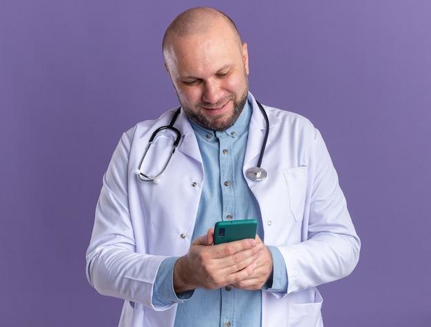 Zufriedener männlicher arzt mittleren alters, der ein medizinisches gewand und ein stethoskop trägt und sein mobiltelefon isoliert auf der lila wand benutzt