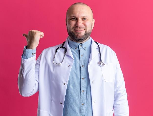 Zufriedener männlicher arzt mittleren alters mit medizinischem gewand und stethoskop, der hinter isoliert auf rosa wand zeigt