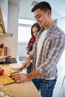 Zufriedener männlicher ehepartner, der für seine frau kocht