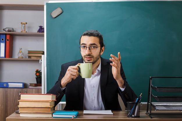 Zufriedener männlicher lehrer mit brille, der eine tasse tee am tisch mit schulwerkzeugen im klassenzimmer hält