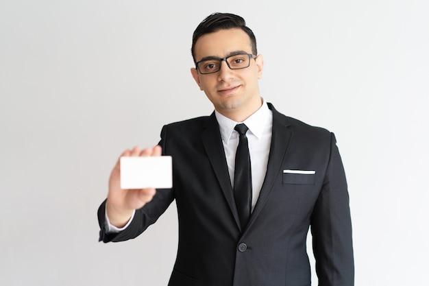 Zufriedener männlicher rechtsanwalt der mischrasse, der visitenkarte zeigt und kamera betrachtet