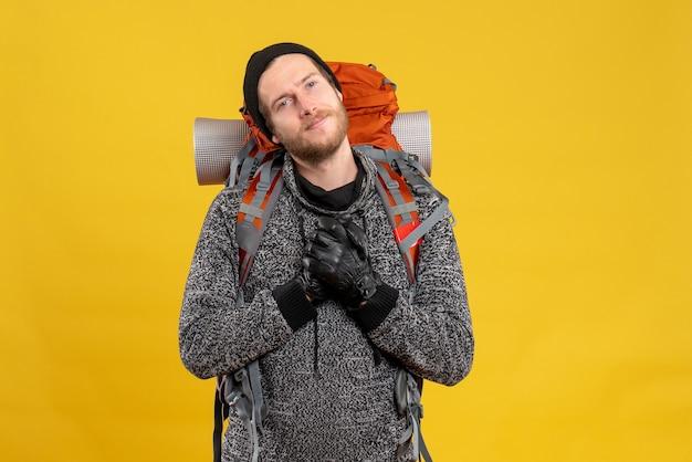 Zufriedener männlicher tramper mit lederhandschuhen und rucksack, der die hände auf die brust legt