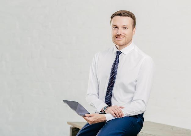 Zufriedener männlicher unternehmer zahlt online auf einem digitalen tablet, gekleidet in elegantes weißes hemd, krawatte und hose, sitzt auf einem holztisch