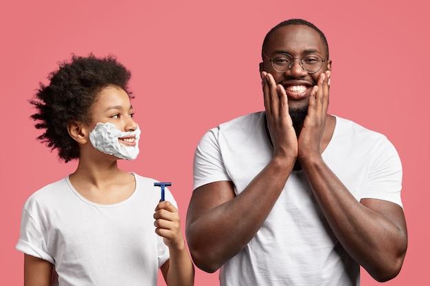 Zufriedener mann berührt die wangen und ist froh, nach der rasur eine weiche haut zu haben. glücklicher teenager hält rasiermesser und wird sich zum ersten mal rasieren