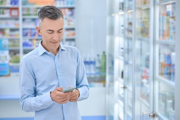 Zufriedener mann, der eine sms in der apotheke liest