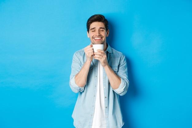 Zufriedener mann, der eine tasse tee oder kaffee genießt, eine tasse mit einem zufriedenen lächeln hält und vor blauem hintergrund steht