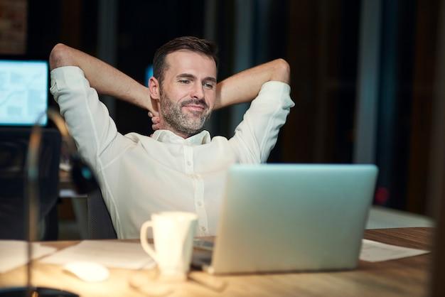 Zufriedener mann, der in seinem büro ruht