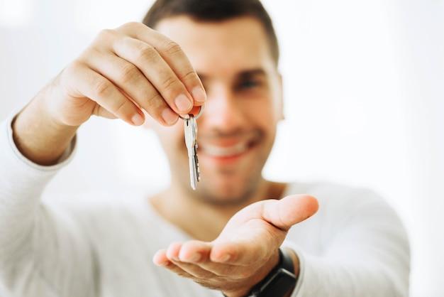 Zufriedener mann, der neue schlüssel hält