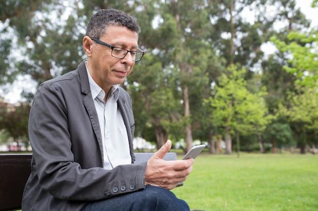 Zufriedener mann, der smartphone verwendet und auf bank im park sitzt