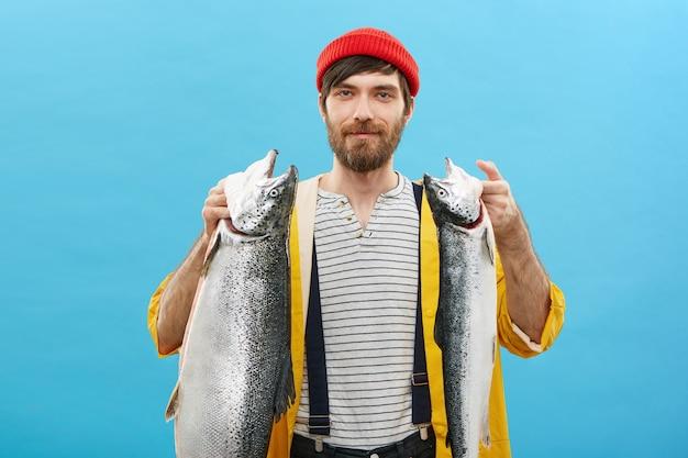 Zufriedener mann, der zwei große fische hält, die erfolgreichen tag haben