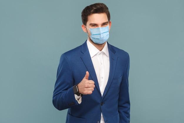 Zufriedener mann mit chirurgischer medizinischer maske, die wie zeichen daumen hoch in die kamera zeigt. geschäftsleute medizin und gesundheitskonzept. indoor, studioaufnahme auf hellblauem hintergrund