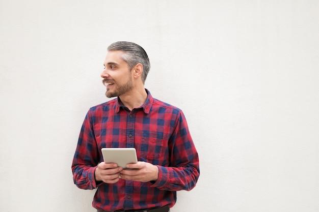 Zufriedener mann mit der digitalen tablette, die beiseite schaut
