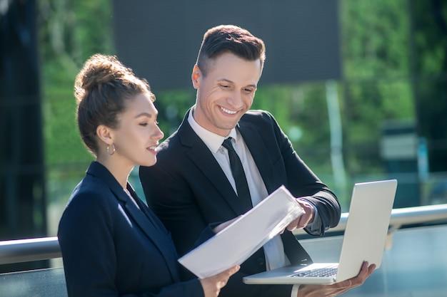 Zufriedener mann mit laptop und frau mit papieren