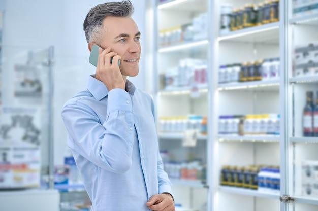 Zufriedener mann mittleren alters beim telefonieren in der apotheke