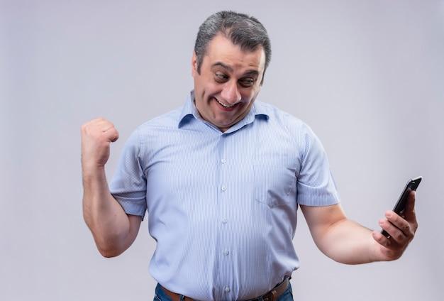 Zufriedener mann mittleren alters, der blaues vertikal gestreiftes hemd trägt, das sein handy betrachtet und eine geballte faust mit einer handbewegung im stehen zeigt