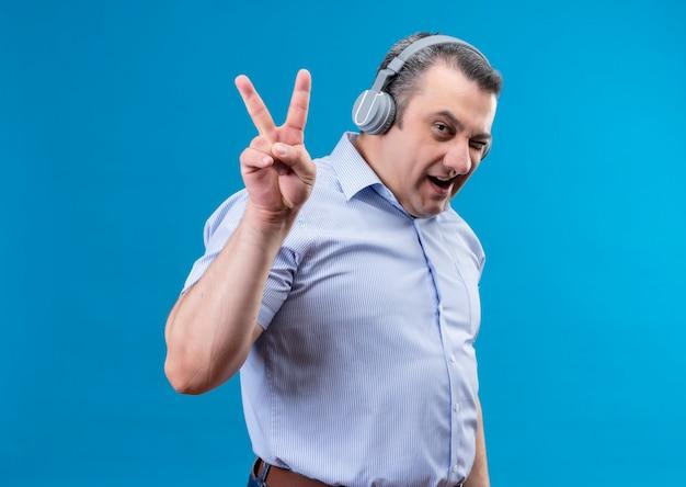 Zufriedener mann mittleren alters in blau gestreiftem hemd in kopfhörern, die in die kamera schauen und handbewegung mit erhobenen zwei fingern auf einem blauen raum