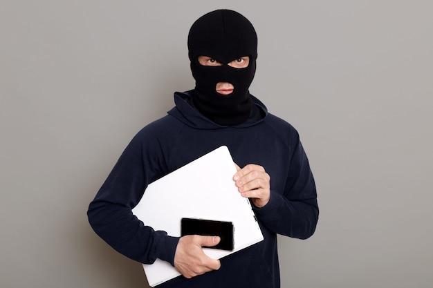 Zufriedener mann räuber stiehlt laptop buche und telefon