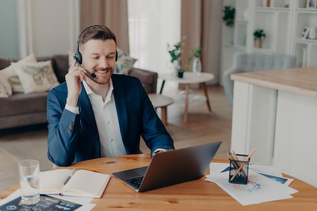 Zufriedener professioneller bärtiger männlicher unternehmer beobachtet online-webinar für bildungsunternehmen mit headset-lookat laptop hat entfernte computerarbeit. fernschulungs- und webkonferenzkonzept