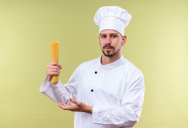 Zufriedener professioneller männlicher kochkoch in der weißen uniform und im kochhut, die rohe spaghetti-nudeln darstellen, die über grünem hintergrund stehen
