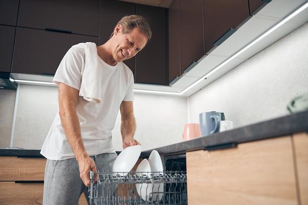 Zufriedener reifer mann, der ein lächeln auf seinem gesicht behält, während er zu hause teller in die spülmaschine stellt