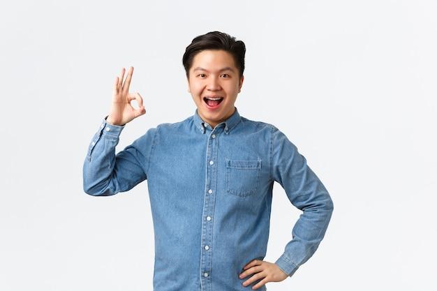 Zufriedener selbstbewusster lächelnder asiatischer kerl mit zahnspange, der eine gute geste zeigt, eine perfekte arztklinik empfehlen, großartige stomatologie, mit den ergebnissen zufrieden sein, weißer hintergrund erstaunt stehen