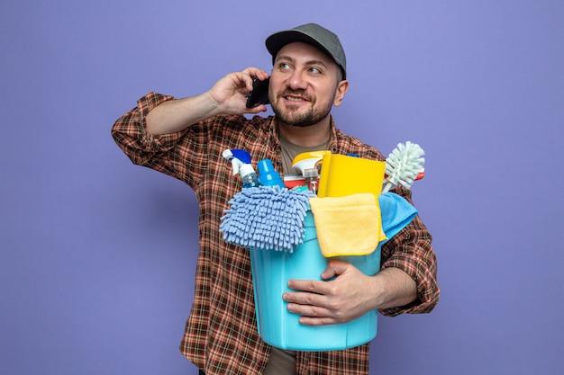 Zufriedener slawischer reinigungsmann, der reinigungsgeräte hält und am telefon mit blick auf die seite spricht